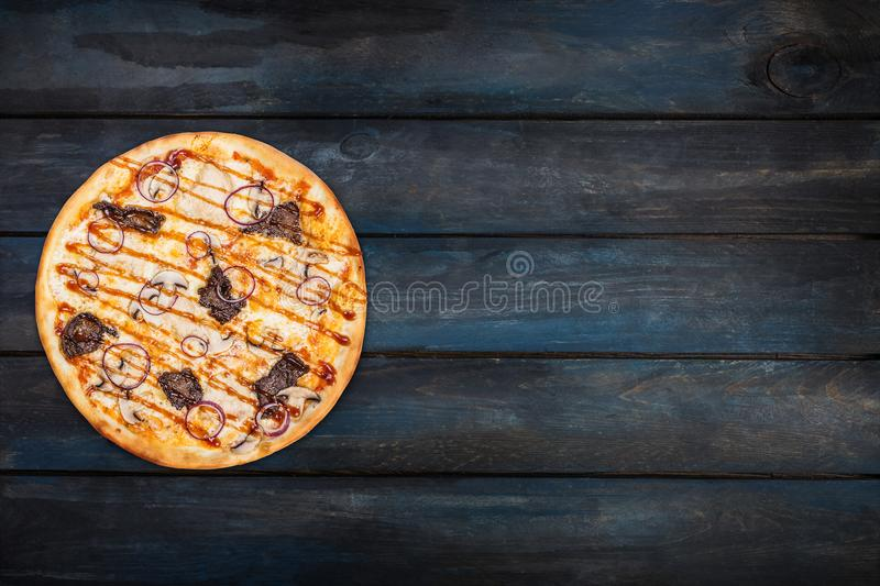 Delicious pizza with mushrooms chicken meat and onions on a dark background. Top view orientation on the left side stock photos