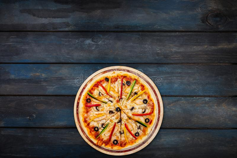 Delicious pizza with mushrooms chicken sweet peppers and olives on a dark wooden background. Top view bottom orientation stock photography