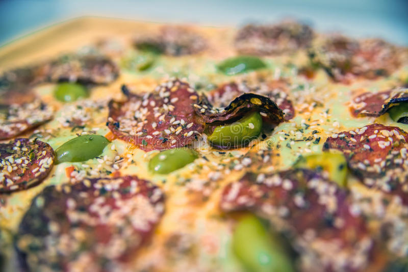 Delicious pizza served on wooden table. hot tasty delicious. Rustic homemade american pizza with tomato gherkin salami olives royalty free stock image