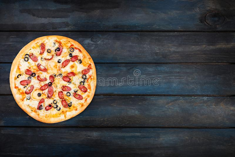 Delicious pizza with smoked sausage and olives on a dark wooden background. Top view orientation on the left side royalty free stock photos