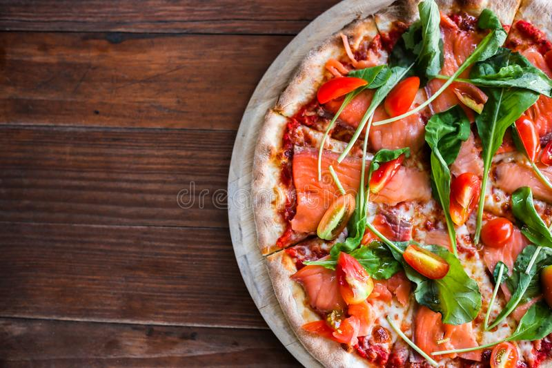 Delicious pizza on top view. Yummy pizza with tomatoes, vegetables, cheese and smoke salmon on wooden table at pizzeria. It'€™ royalty free stock images