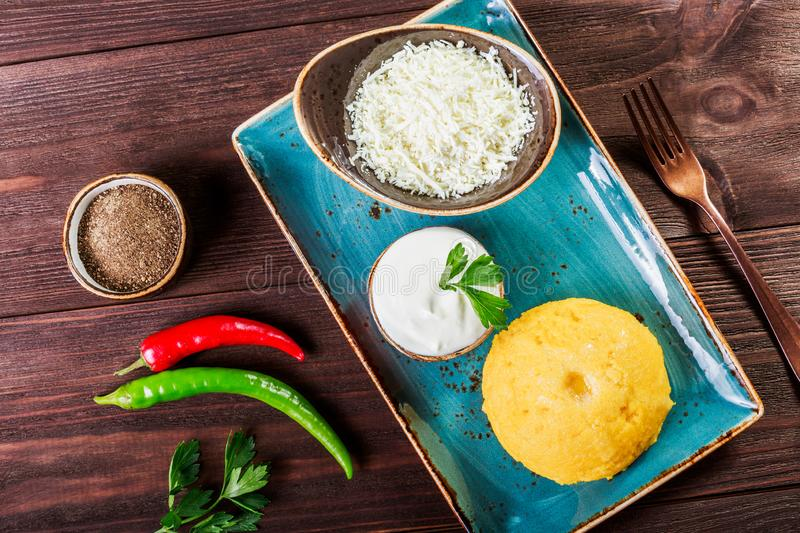 Delicious polenta - Corn porridge hominy with goat cheese, butter and sour cream on wooden background. Healthy food. Top view royalty free stock photography