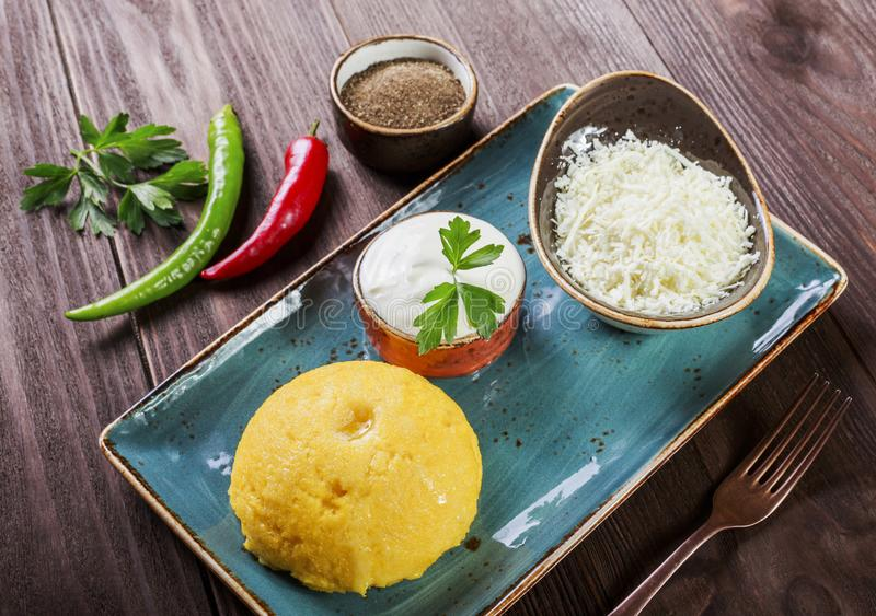 Delicious polenta - Corn porridge hominy with goat cheese, butter and sour cream on wooden background. Healthy food. Top view stock photography