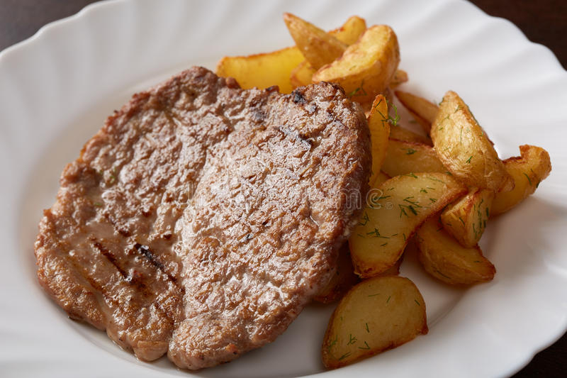 Delicious pork chop and potato wedges, close-up stock photography