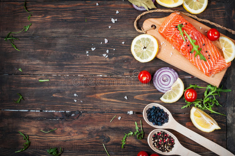Delicious portion of fresh salmon fillet with aromatic herbs, spices and vegetables - healthy food, diet or cooking concept. Top v. Iew and copyspace stock photography