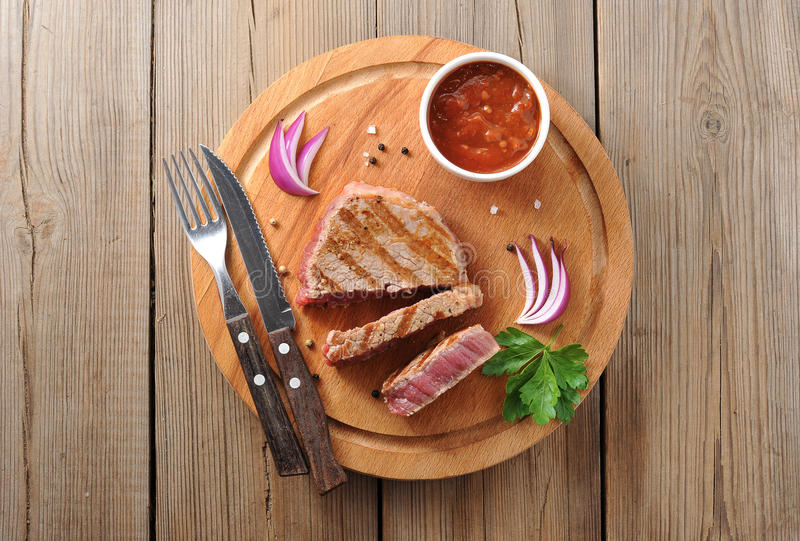 Delicious portion of healthy grilled lean medium rare beef steak. Cut through and served on a wooden kitchen board royalty free stock images