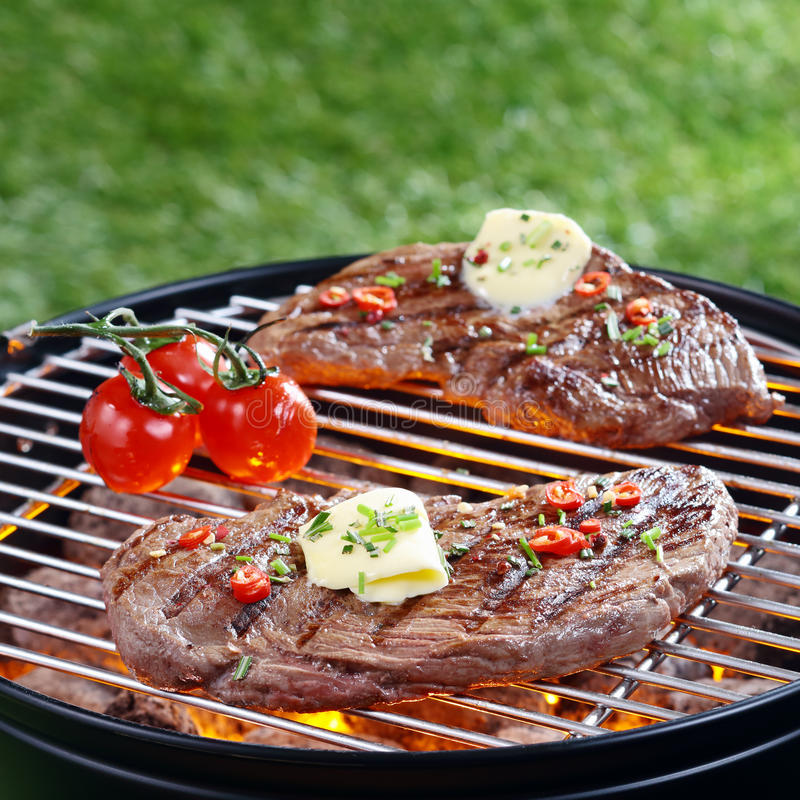 Delicious steak grilling on a barbecue royalty free stock photos
