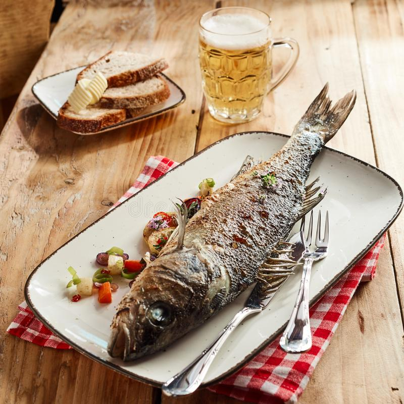Delicious pub lunch with grilled sea bass. Delicious pub lunch with whole grilled sea bass served on a platter with a tankard of cold frothy beer and rye bread stock photos
