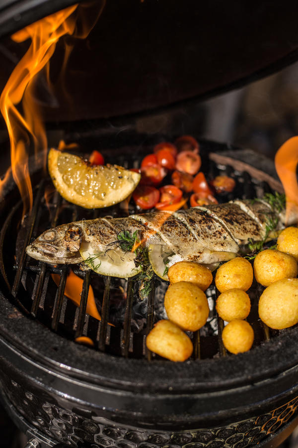 Delicious rainbow trout fish with tomatoes, potatoes and lemon cooking on hot flaming grill. Barbecue. Restaurant. Delicious rainbow trout fish with tomatoes stock photography