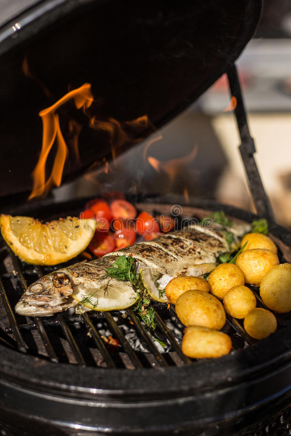 Delicious rainbow trout fish with tomatoes, potatoes and lemon cooking on hot flaming grill. Barbecue. Restaurant. Delicious rainbow trout fish with tomatoes stock images