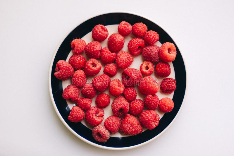 Delicious raspberries on a plate with white background stock photography
