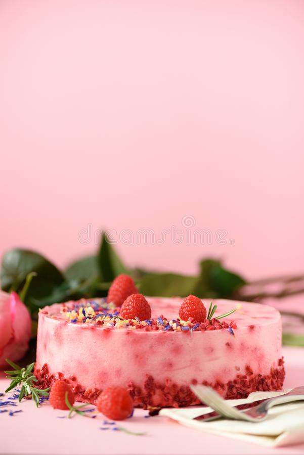 Delicious raspberry cake with fresh berries, rosemary and dry flowers on pink background. Copy space for your text. Vegetarian, stock image