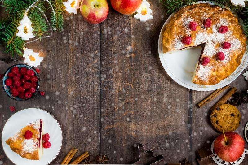 Delicious Christmas raspberry pie with berry filling and icing sugar and spices on a dark background. Delicious raspberry pie with berry filling and icing sugar royalty free stock image