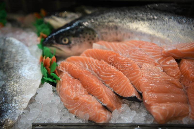 Delicious raw salmon fish fillets with whole fish partly in the background. Taken in a fishmongers in southern England UK. With cut and sliced fresh salmon royalty free stock image