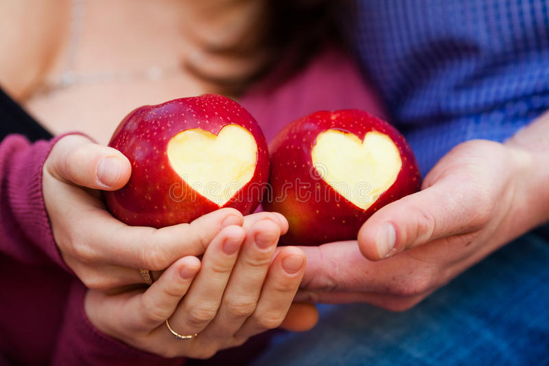 Delicious red apple with symbolic heart cutout on rough. In hands royalty free stock photos
