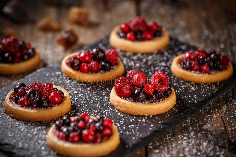 Delicious red berries mini tarts stock photography