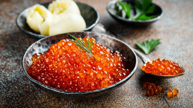 Delicious red caviar in black bowl on a dark concrete background.  royalty free stock photos