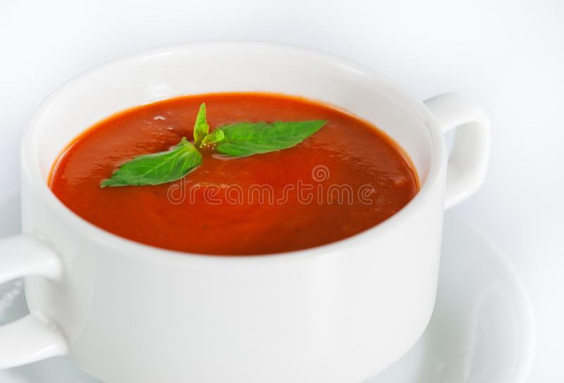 Delicious red tomato soup in bowl on white. Background royalty free stock photography