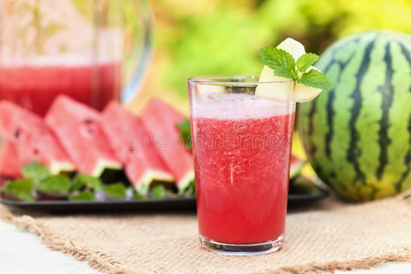 Delicious refreshing summer fruit - watermelon juice and slices on the table stock photos