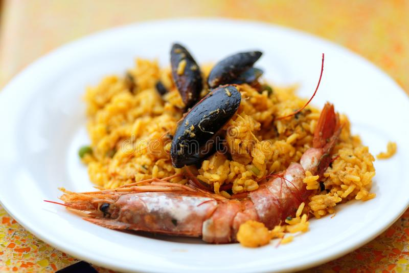 Delicious rice dish with mussels and royal prawns stock image