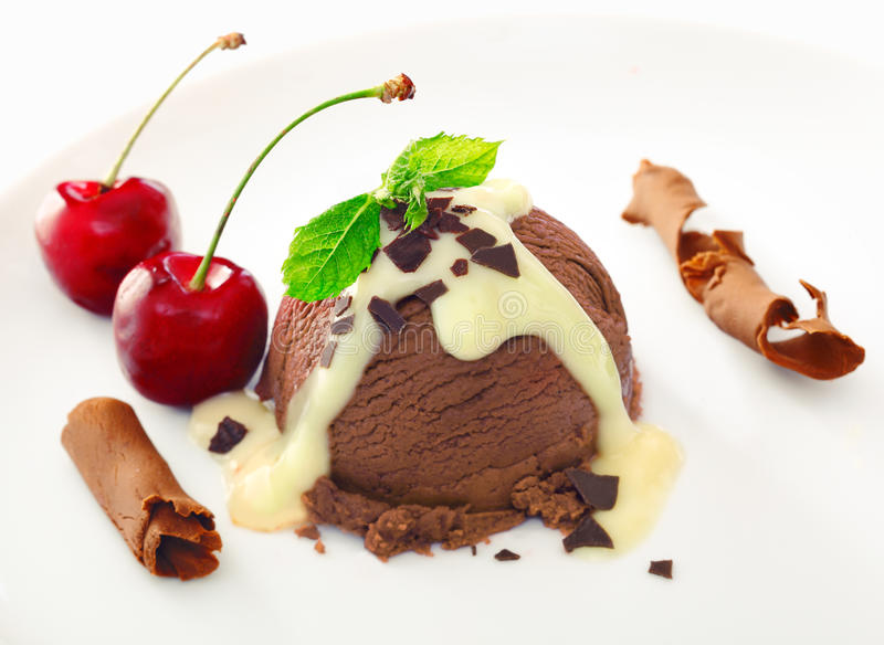 Delicious rich chocolate icecream dessert. Drizzled with sauce and served with ripe red cherries and coiled shavings of milk chocolate royalty free stock photos