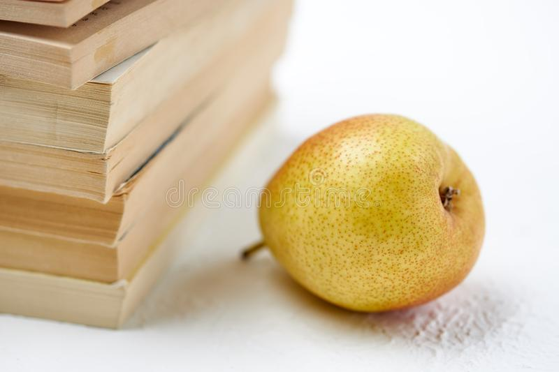 Delicious ripe pear lies next to a stack of books stock photography