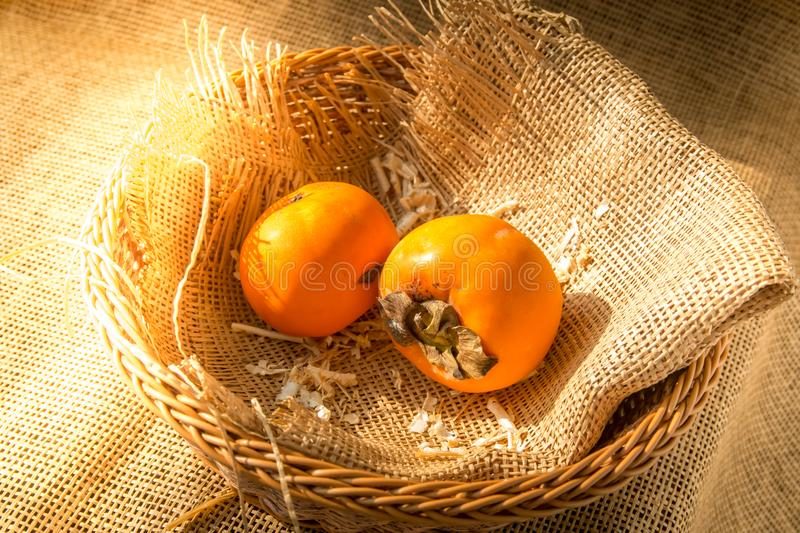 Delicious ripe persimmon fruit in basket wrapped with burlap textile with morning sunshine. royalty free stock image