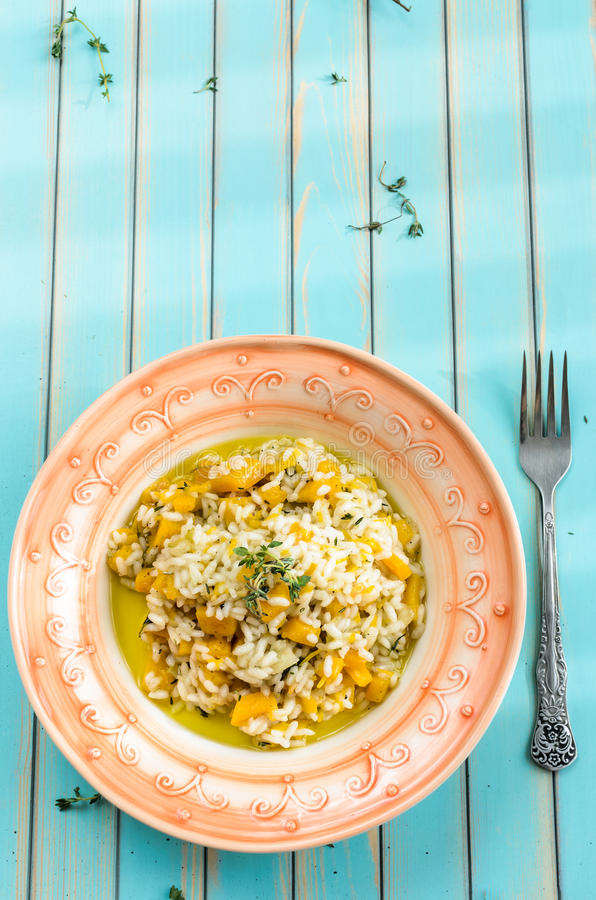 Delicious risotto with ripe pumpkin over wooden turquoise background stock photo