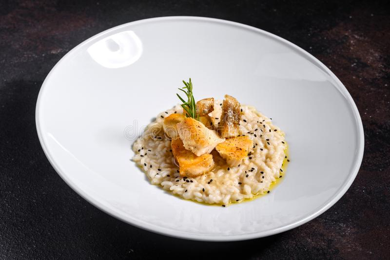 Delicious risotto with roasted pieces of chicken fillet stock image