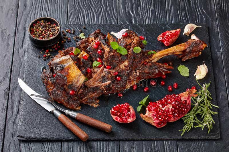 Delicious roast leg of lamb with spices and rosemary on a black slate plate on a wooden table,view from above, close-up royalty free stock photography