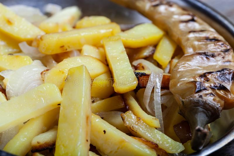 Delicious roast potatoes with onion and spices in a pan on kitchen towel on the old wooden table. Traditional rural dinner.  royalty free stock photography