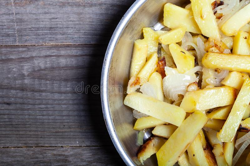 Delicious roast potatoes with onion and spices in a pan on kitchen towel on the old wooden table. Traditional rural dinner.  stock image
