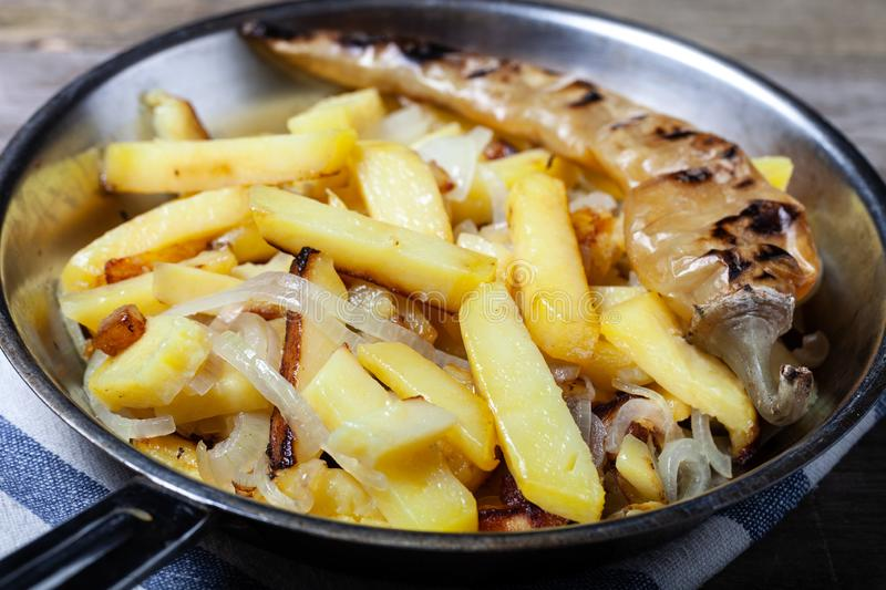 Delicious roast potatoes with onion and spices in a pan on kitchen towel on the old wooden table. Traditional rural dinner.  royalty free stock images