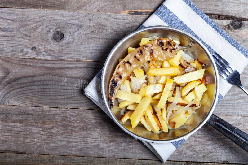 Delicious roast potatoes with onion and spices in a pan on kitchen towel on the old wooden table. Traditional rural dinner.  royalty free stock photos