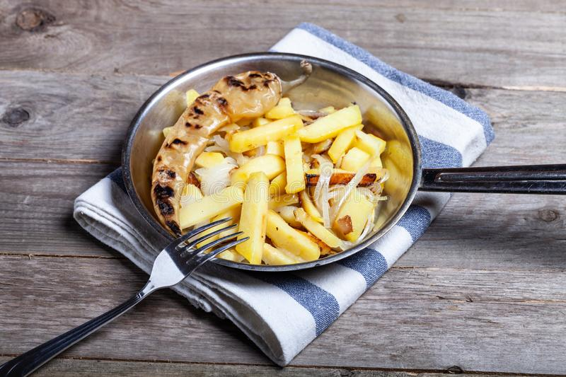 Delicious roast potatoes with onion and spices in a pan on kitchen towel on the old wooden table. Traditional rural dinner.  stock photography