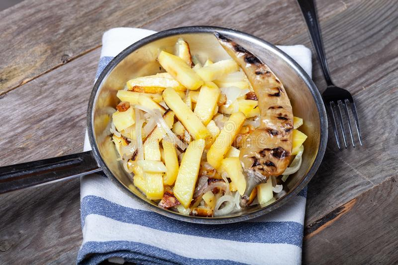 Delicious roast potatoes with onion and spices in a pan on kitchen towel on the old wooden table. Traditional rural dinner.  royalty free stock image