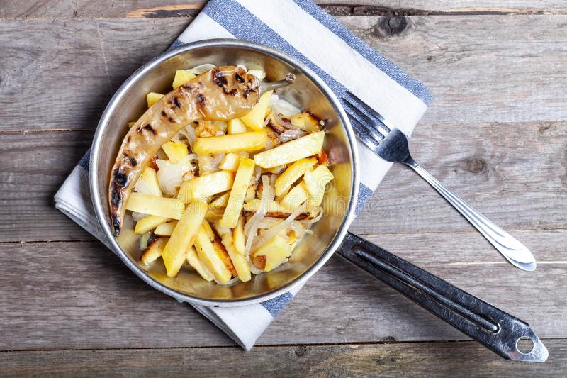 Delicious roast potatoes with onion and spices in a pan on kitchen towel on the old wooden table. Traditional rural dinner.  stock photo