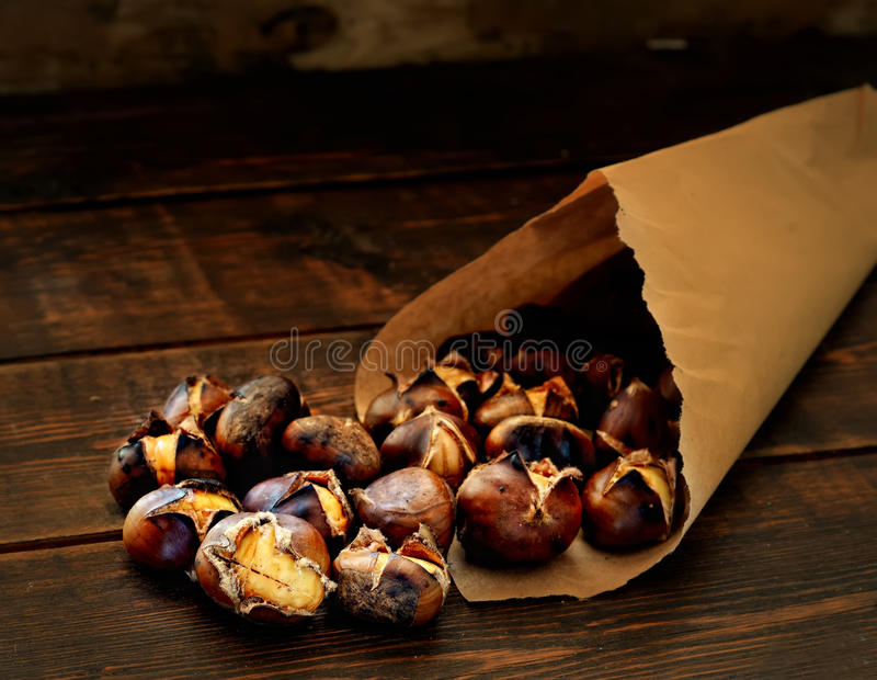 Delicious roasted chestnuts in paper bags on wooden background royalty free stock photography