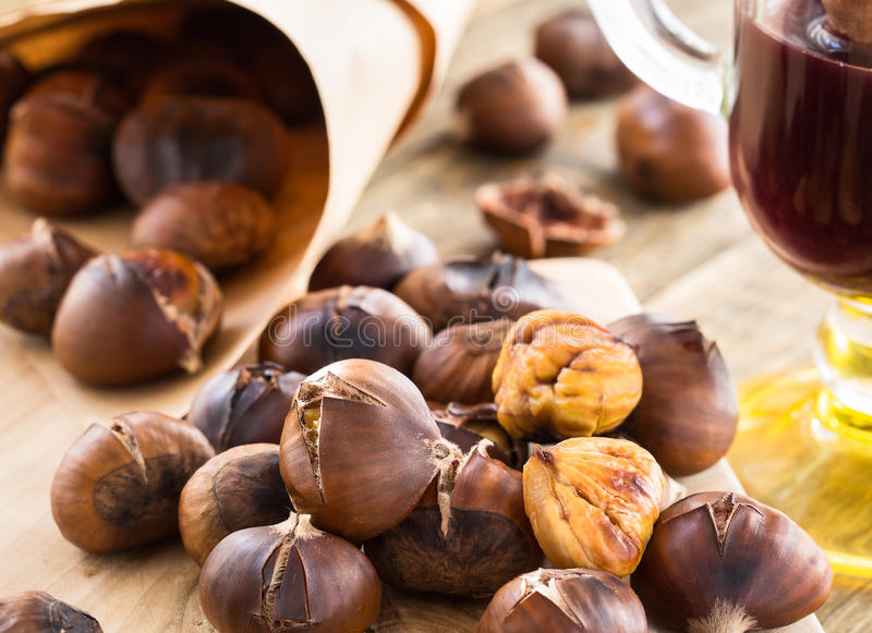 Delicious roasted chestnuts on wooden board royalty free stock photography