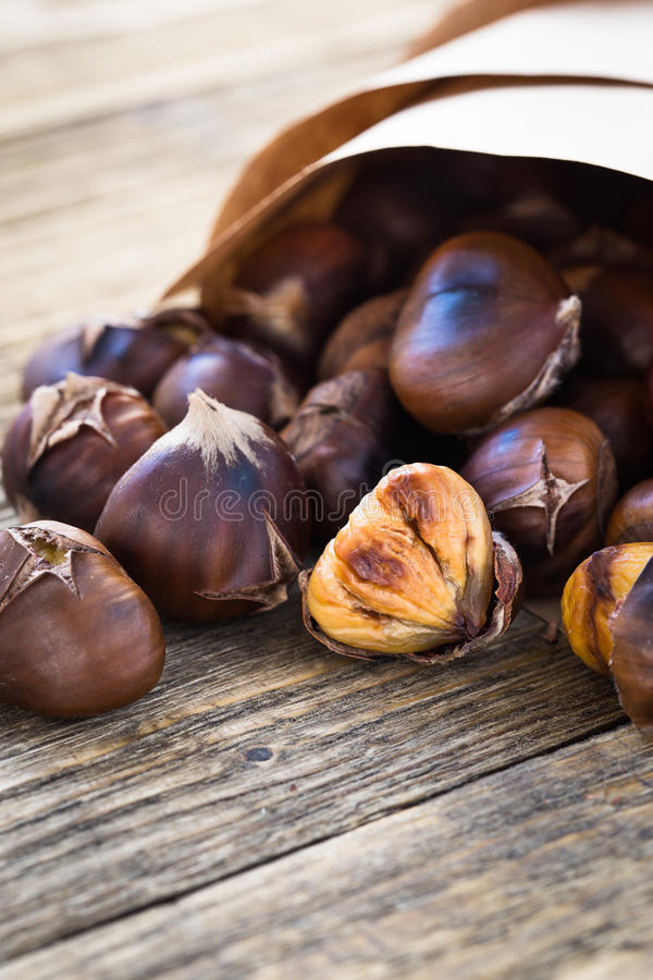 Delicious roasted chestnuts on wooden board royalty free stock images