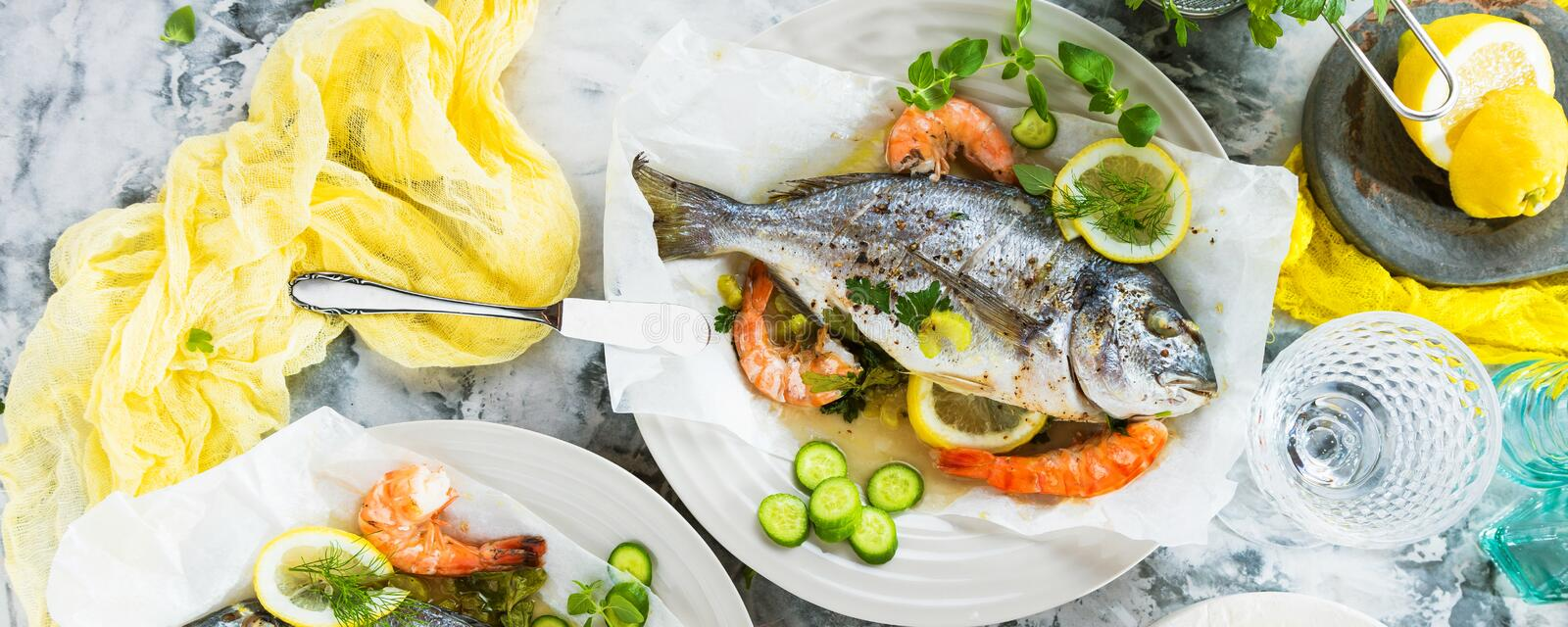Delicious roasted dorado or sea bream fish with lemon and fresh Prawns , fresh parsley and spinach on white platter . royalty free stock photos