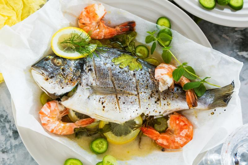 Delicious roasted dorado or sea bream fish with lemon and fresh Prawns , fresh parsley and spinach on white platter . royalty free stock photo