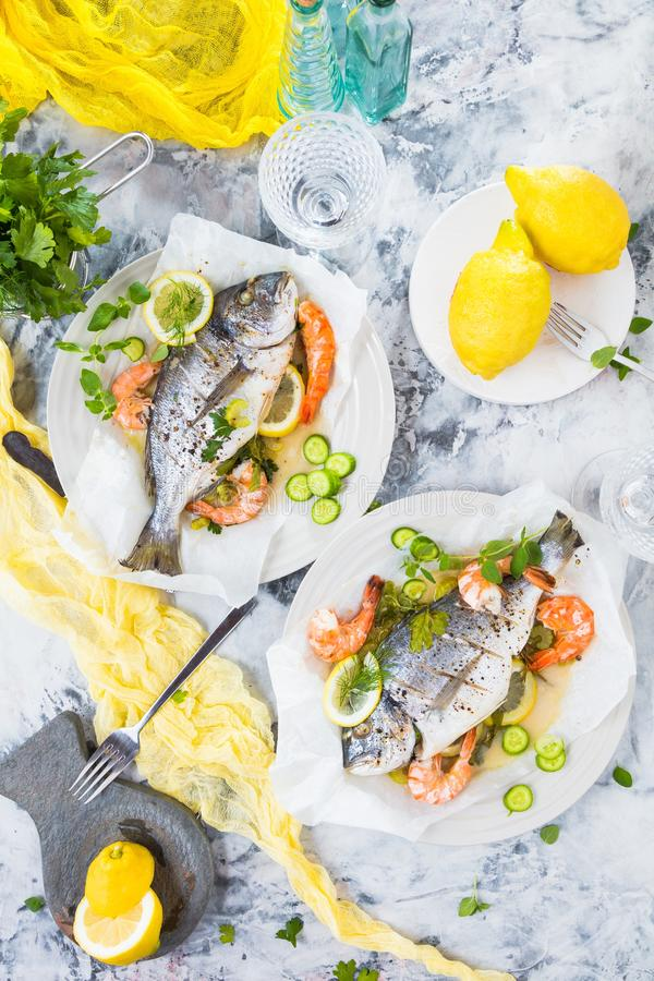 Delicious roasted dorado or sea bream fish with lemon and fresh Prawns , fresh parsley and spinach on white platter . royalty free stock images