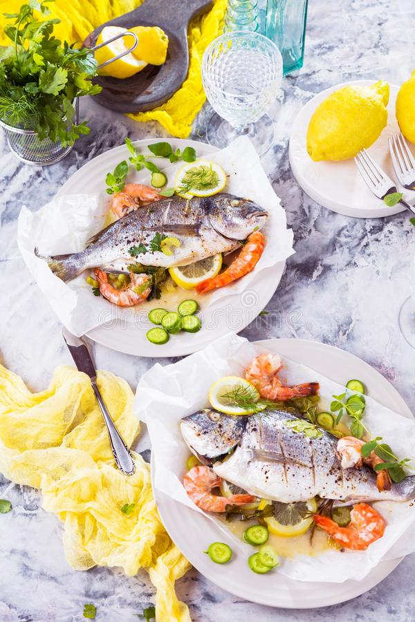 Delicious roasted dorado or sea bream fish with lemon and fresh Prawns , fresh parsley and spinach on white platter . stock photos