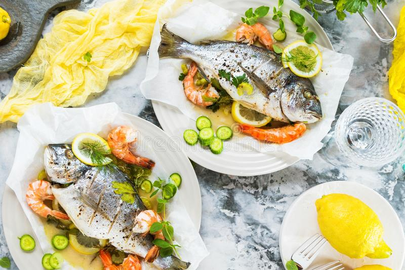 Delicious roasted dorado or sea bream fish with lemon and fresh Prawns , fresh parsley and spinach on white platter . stock image