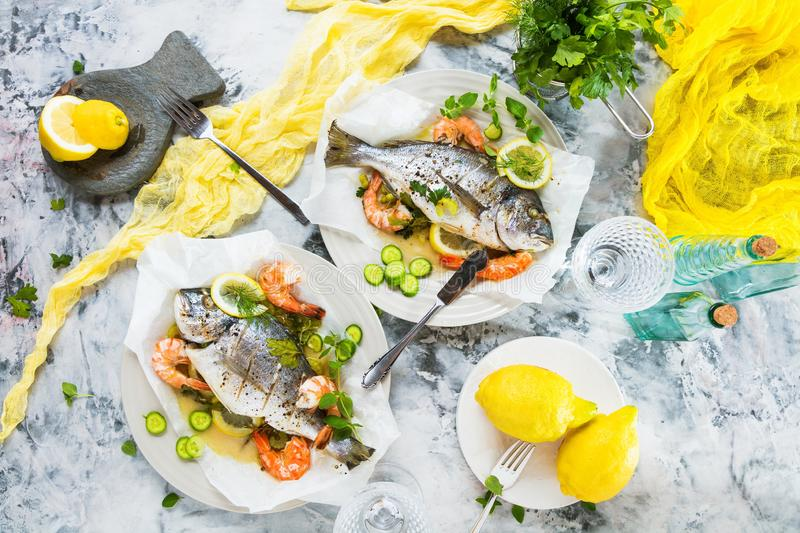 Delicious roasted dorado or sea bream fish with lemon and fresh Prawns , fresh parsley and spinach on white platter . Delicious roasted dorado or sea bream fish royalty free stock image