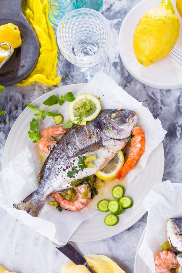Delicious roasted dorado or sea bream fish with lemon and fresh Prawns , fresh parsley and spinach on white platter . stock photography