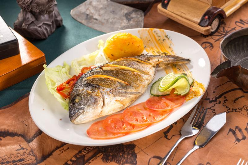 Delicious roasted dorado or sea bream fish with orange slices on white plate on old map background stock images