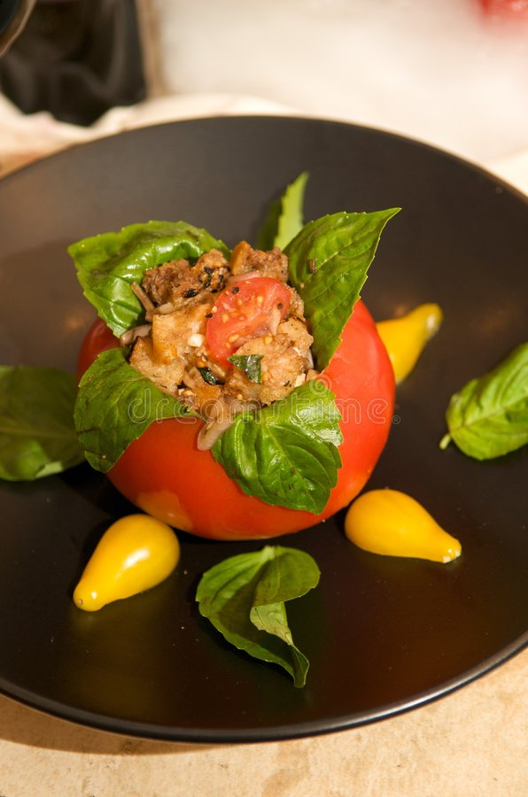 Delicious roma tomato stuffed with basil and chick stock image