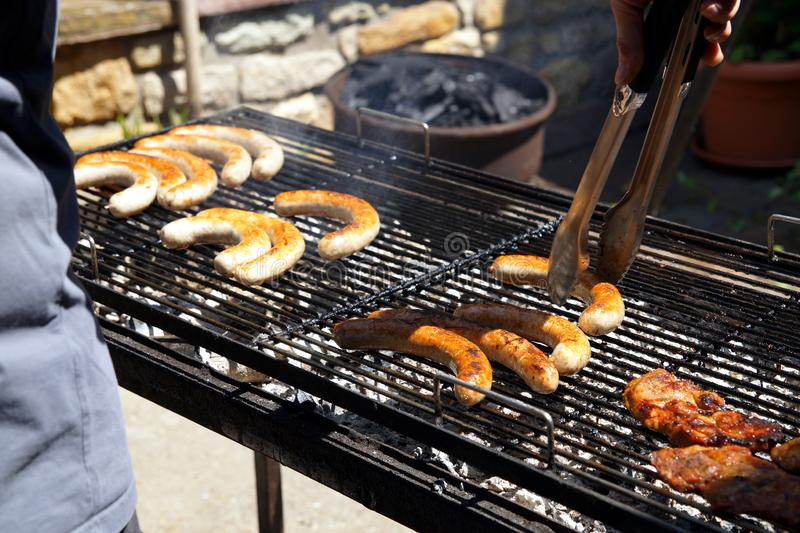 Delicious row of pork bratwurst and grilled meat over the coals on barbecue.lifting a pair of tongs in a view of his hand. stock photo